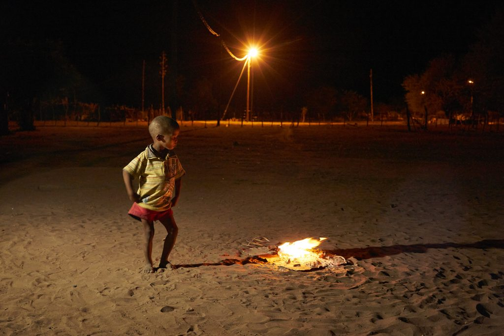 A 5 year-old boy performs around a small fire in the dry landscape of the Blouberg Resettlement Farm, Omaheke Region, Namibia