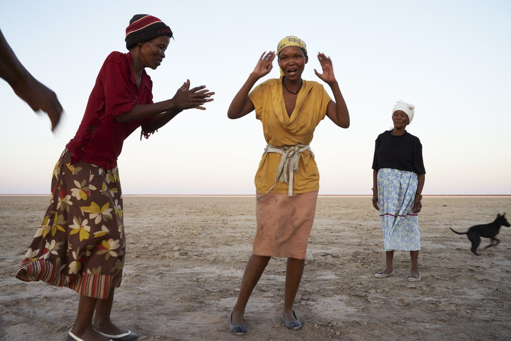 """During a six-year drought, Juǀ'hoansi women Kanis Witbooi, Selma Jacobs and Eva Isaak join in to perform a Women perform a Rain Dance on the Omongwa (""""Salt"""") Pan"""